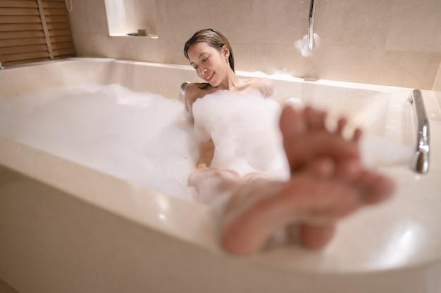 Vrouw liggend in badkuip en ontspannen met bubbelschuim.