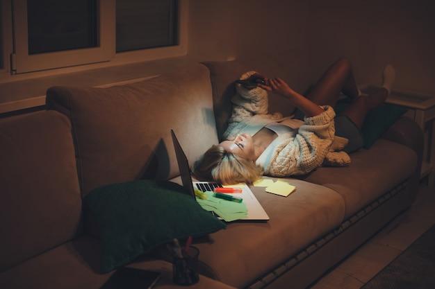 Vrouw liggend in bed chatten op de telefoon 's avonds laat na huiswerk met behulp van een laptop