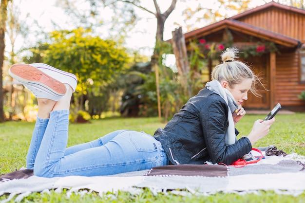 Vrouw liggend in de tuin. jonge blonde vrouw met haar mobiele telefoon buitenshuis. welzijn en buitenshuis concept.