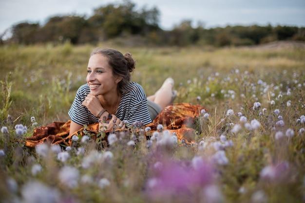 Vrouw liggend in een veld met bloemen overdag