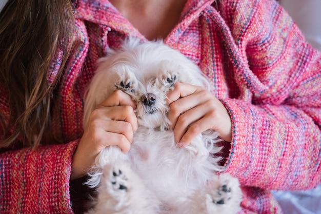Vrouw liggend op bed met haar schattige maltese hond bovendien