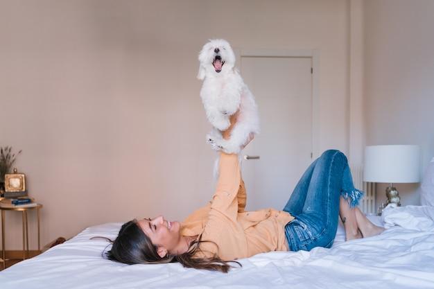 Vrouw liggend op bed met haar schattige maltese hond
