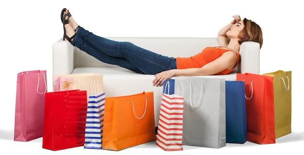 Vrouw liggend op de bank achter een rij tassen moe na het winkelen