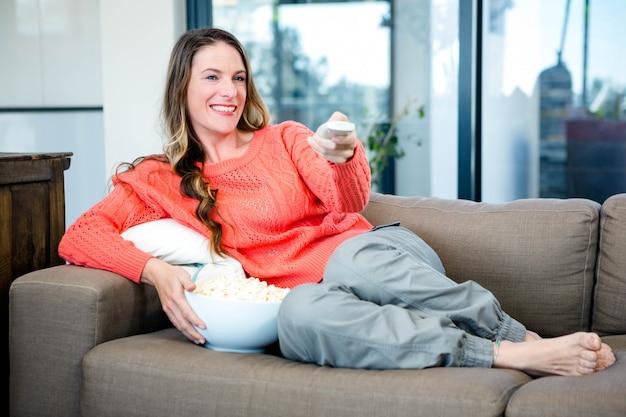 Vrouw liggend op de bank in de woonkamer met popcorn