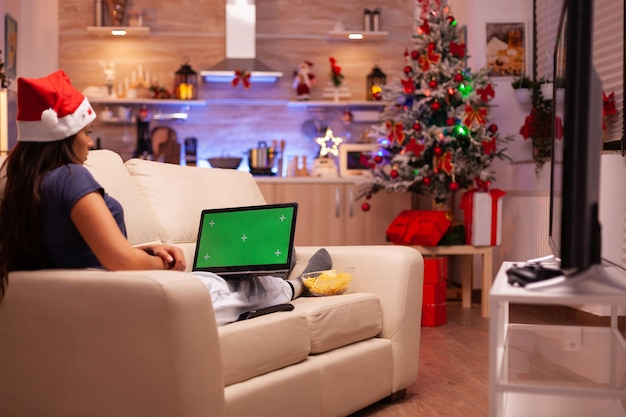Vrouw liggend op de bank kijkend naar groen scherm mock-up chroma key laptop