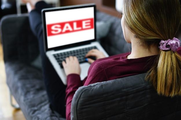 Vrouw liggend op de bank met laptop pc bezoekt de webpagina van de kledingwinkel op internet