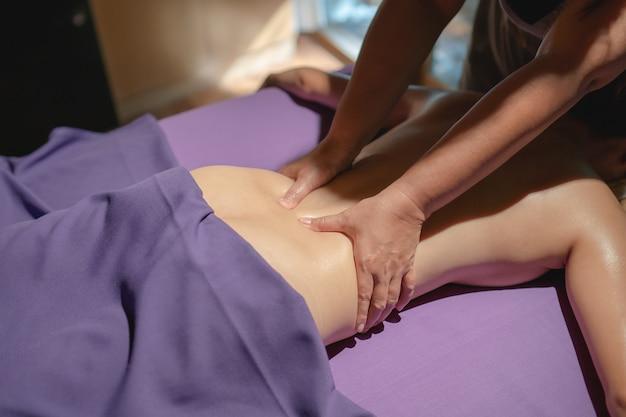 Vrouw liggend op de massagetafel. ontspannende rugmassage in de spa, helende lichaamsbehandeling.