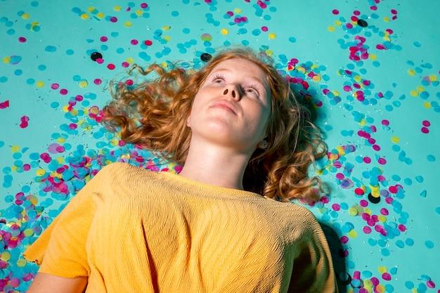Vrouw liggend op de vloer met confetti om haar heen
