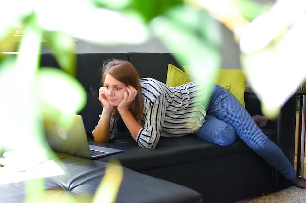 Vrouw liggend op een bank in de tuin van het huis met een laptop werkt