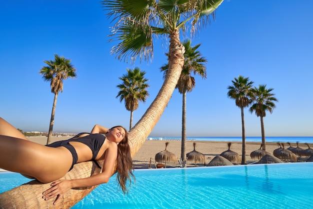 Vrouw, liggend op het zwembad gebogen palmboomstam