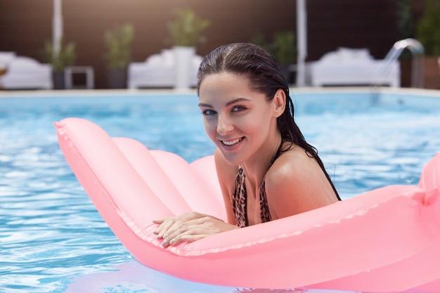Vrouw liggend op watermatras in zwembad, camera kijken met charmante glimlach, poseren met natte haren, rust op zomerverblijf