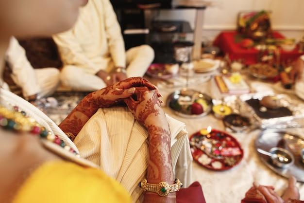 Vrouw ligt haar mooie handen bedekt met mehndi over haar knie