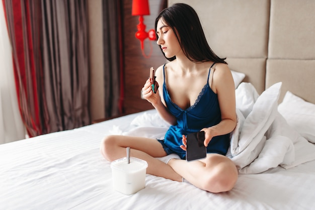 Vrouw ligt in bed en eet snoep, depressie