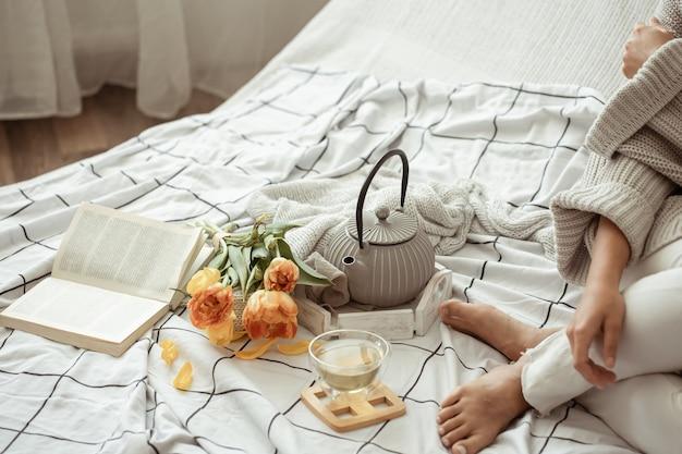 Vrouw ligt in bed met thee, een boek en een boeket tulpen