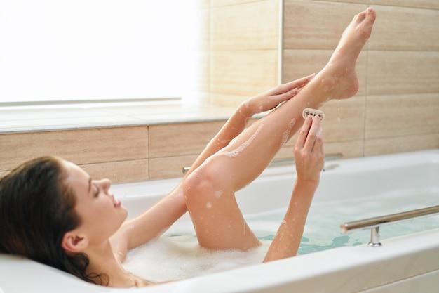 Vrouw ligt in de badkamer ontharing ontspannen interieur