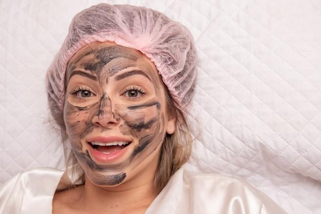 Vrouw ligt in het kantoor van de schoonheidsspecialist over de procedure om haar gezicht te hydrateren. de schoonheidsspecialist brengt een vochtinbrengend masker aan op het gezicht van de patiënt.