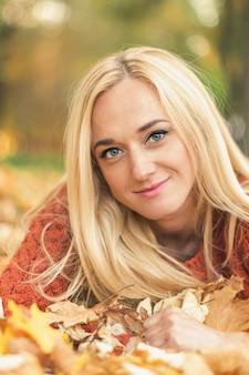 Vrouw ligt op bladeren in de herfst park