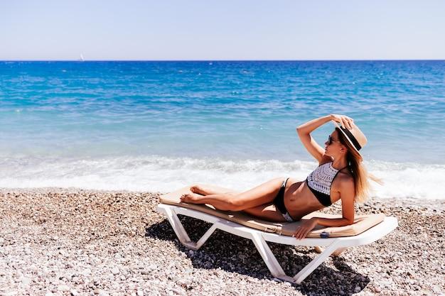 Vrouw ligt op een zonnebank aan zee