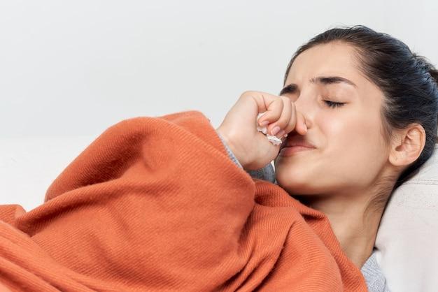 Vrouw ligt op het bed bedekt met een deken koude behandeling