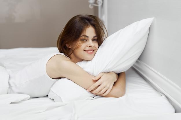 Vrouw ligt op het bed en knuffelt een kussen