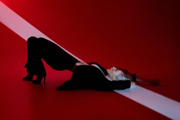 Vrouw ligt op rode achtergrond met lichtstraal op gezicht. sexy naakt en zelfverzekerde blonde vrouw in zwarte jas. rood licht