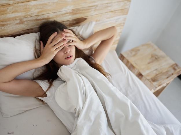 Vrouw ligt 's ochtends in bed bedekt met een deken, handen op haar gezicht