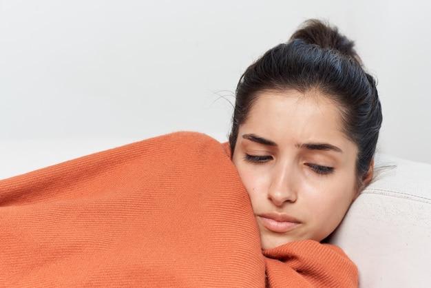 Vrouw ligt thuis op de bank bedekt met een deken met gesloten ogen koud