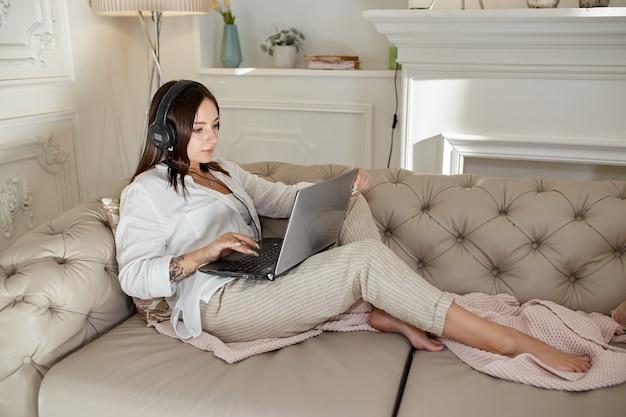 Vrouw ligt thuis op de bank met koptelefoon op en luistert naar muziek