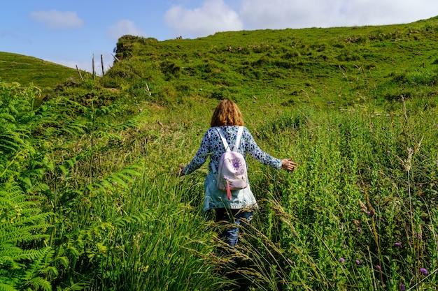 Vrouw loopt door het veld tussen bloemen en groen gras in de zomer grass