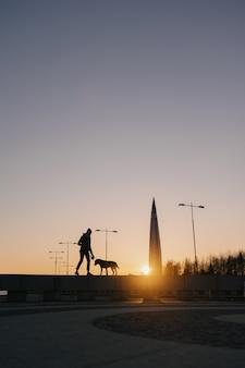 Vrouw loopt haar hond uit bij zonsondergang prachtige zonsondergang tegen de achtergrond van moderne gebouwen