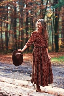 Vrouw loopt in het bos met haar hoed in de hand