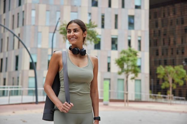 Vrouw loopt in het centrum met fitnessmat gaat aerobicsoefeningen doen gaat oefenen down street ontspant na training sportkleding draagt. mensen levensstijl en fysieke activiteit