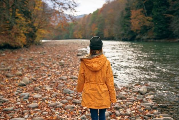 Vrouw loopt langs de rivier herfst bos natuur bergen