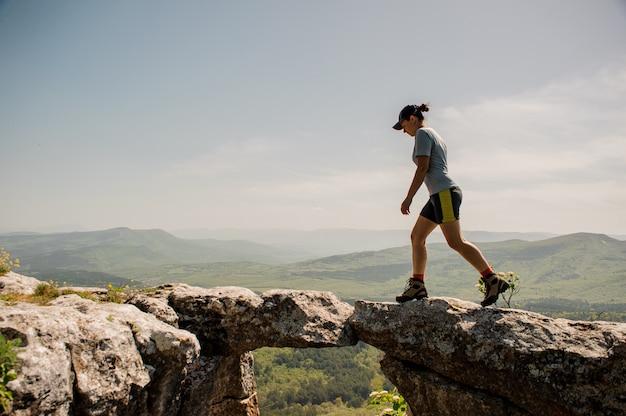 Vrouw loopt langs de rotsachtige bergen