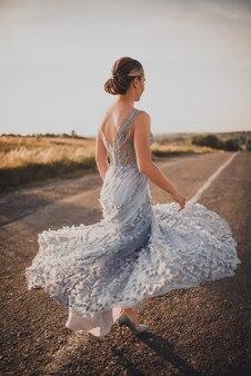 Vrouw loopt langs een asfaltweg in lange jurk bij zonsondergang