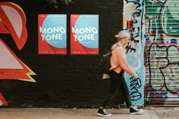 Vrouw loopt langs street art muurschildering en posters