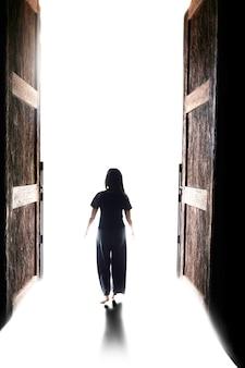 Vrouw loopt naar het licht door de open grote deur