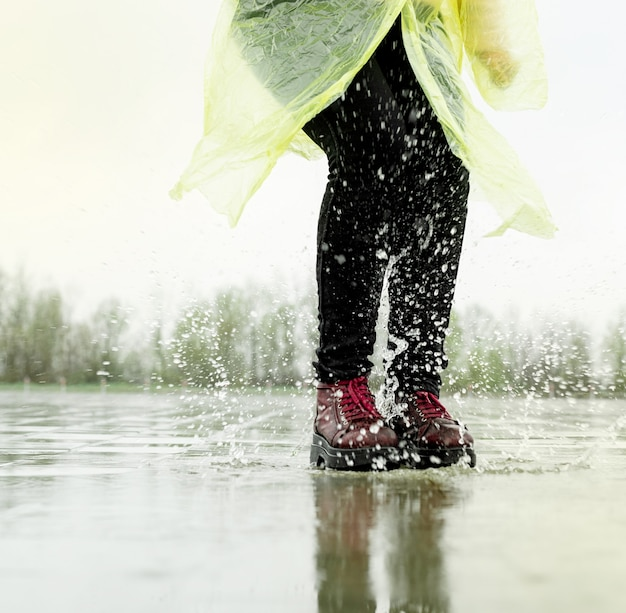 Vrouw loopt op asfalt bij regenachtig weer. close up van benen en schoenen spatten in plassen.