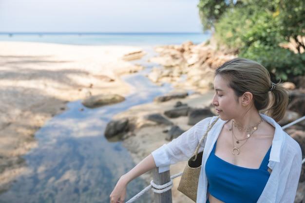 Vrouw loopt op de houten pierbrug aan het strand aan zee.