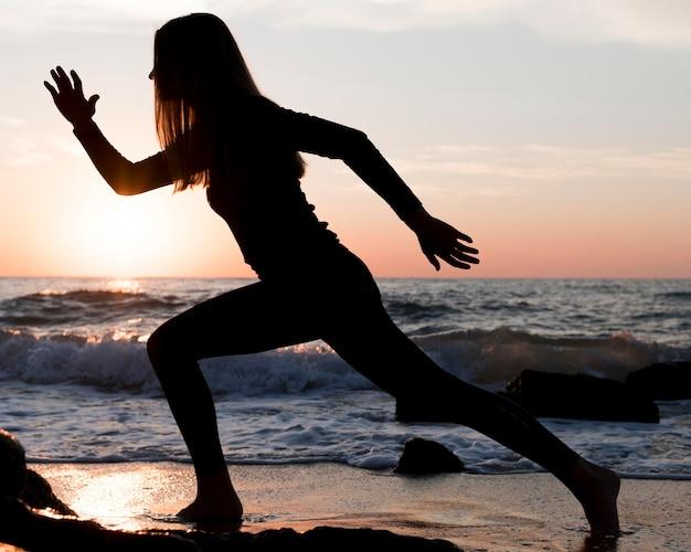 Vrouw loopt op het strand bij zonsondergang