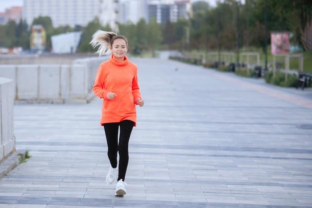 Vrouw loopt op het trottoir in een trainingssessie buiten.