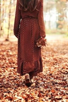 Vrouw loopt weg met een herfstblad