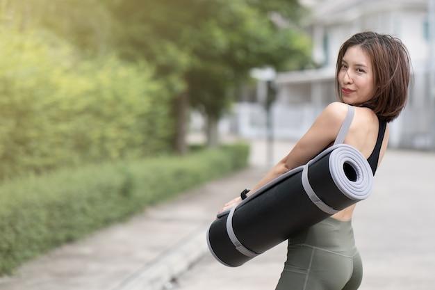 Vrouw lopen naar de sportschool, met fitness mat.