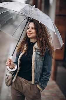 Vrouw lopen onder de paraplu in een regenachtig weer