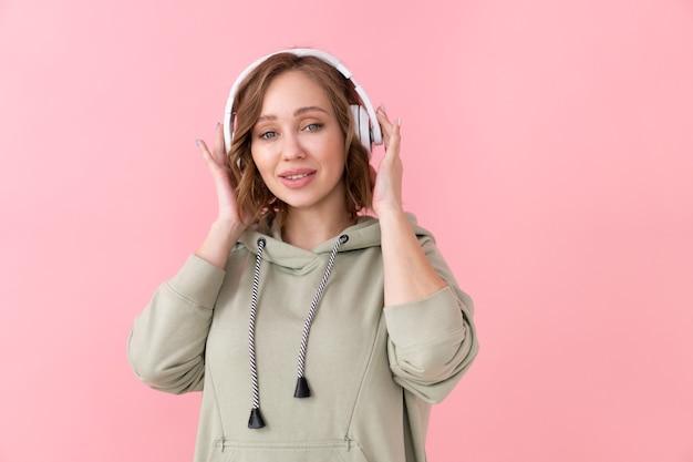 Vrouw luisteren muziek koptelefoon blanke vrouw genieten van podcast of audioboeken gekleed oversized hoodie roze achtergrond