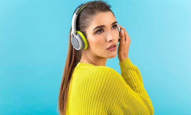 Vrouw luisteren naar muziek in draadloze koptelefoon gelukkig dragen gele gebreide trui poseren op blauw