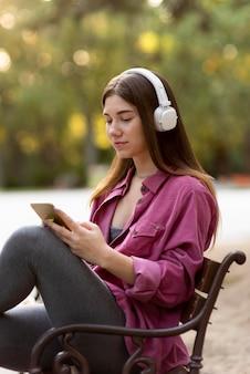 Vrouw luisteren naar muziek in het park