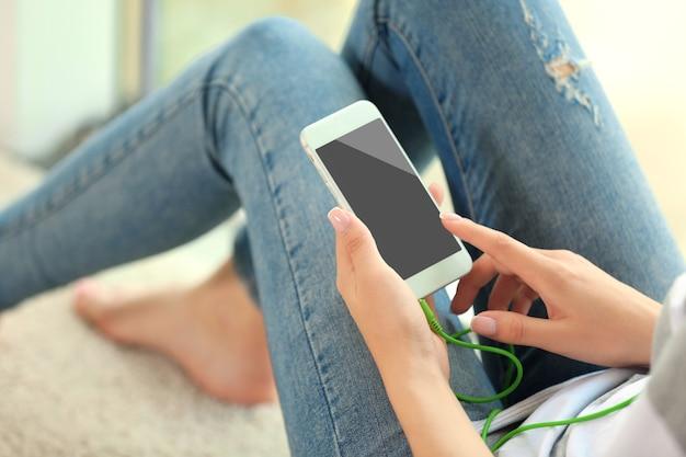 Vrouw luisteren naar muziek op smartphone in de kamer