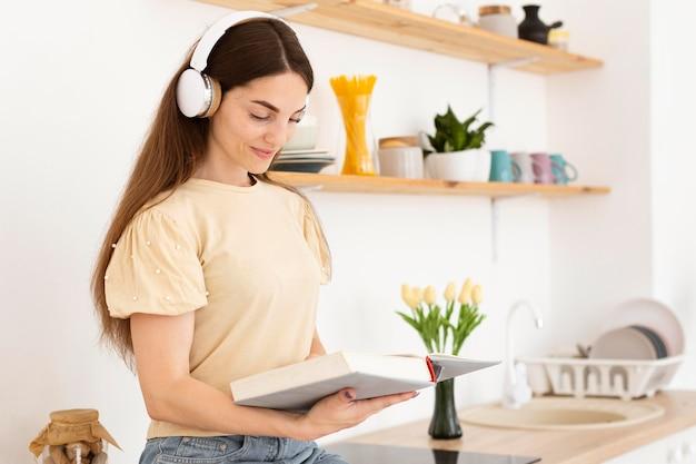 Vrouw luisteren naar muziek via een koptelefoon tijdens het lezen