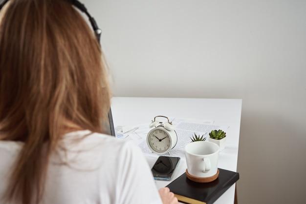 Vrouw luisteren online cursus in de koptelefoon, onderwijs op afstand